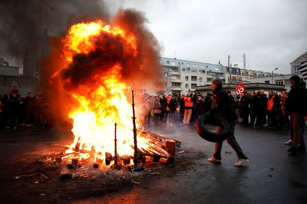 French labour union members and workers on strike stand near a fire as they attend a meeting near the Gare de Lyon train station before a demonstration in Paris during the 36th consecutive day of striking against the French government's pension reform plans in France, 9 January 2020.