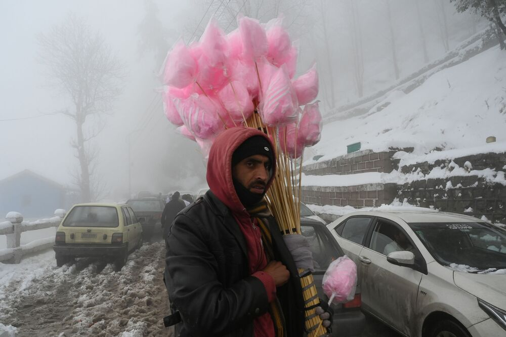 A vendor sells sugar candy on a street during snowfall in Murree, some 65 km north of Islamabad, on 7 January 2020.