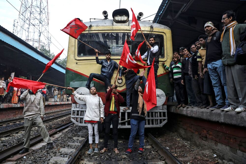 Supporters of the Communist Party of India-Marxist (CPI-M) block a passenger train during an anti-government protest rally organised as part of a nationwide strike by various trade unions in Kolkata, India, 8 January 2020.