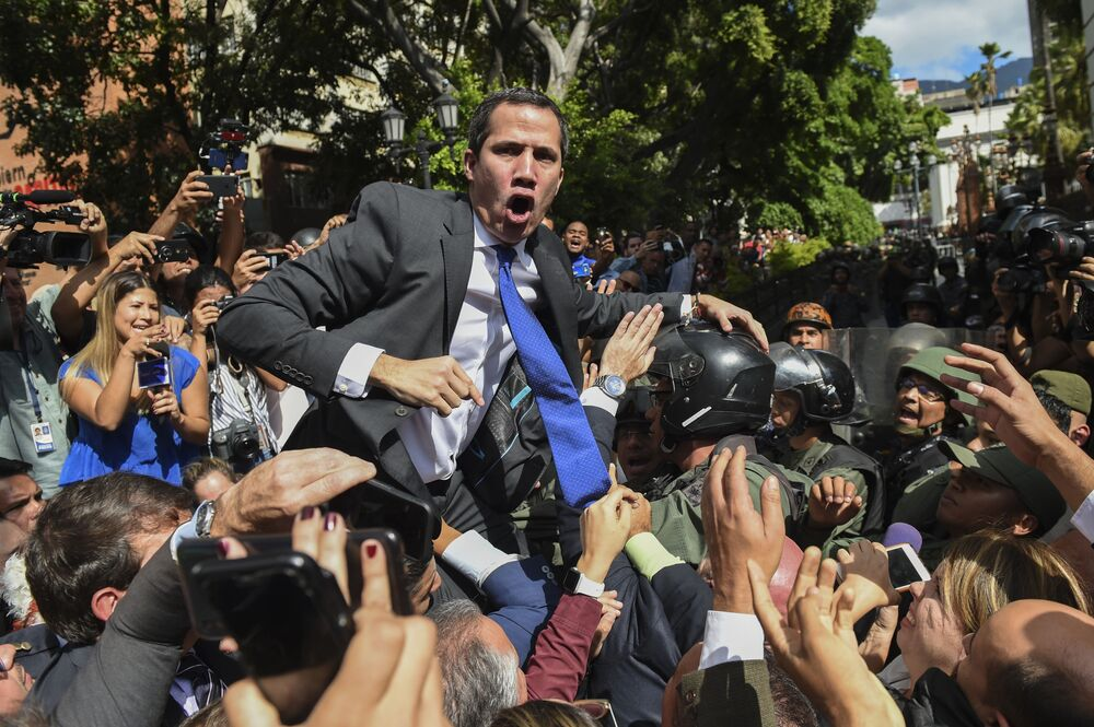 Venezuelan opposition leader and self-proclaimed interim President Juan Guaido shouts while surrounded by journalists on his way to the National Assembly in Caracas on 7 January 2020.