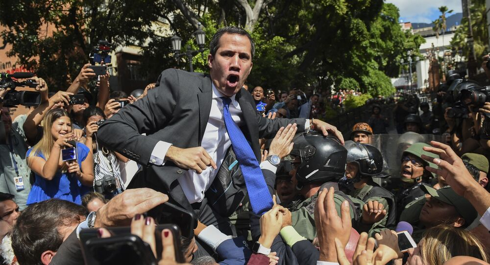 Venezuelan opposition leader and self-proclaimed acting president Juan Guaido shouts surrounded by journalists on his way to the National Assembly, in Caracas, on January 7, 2020.