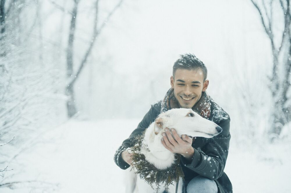 Smiling man with a white dog with winter forest on the background.