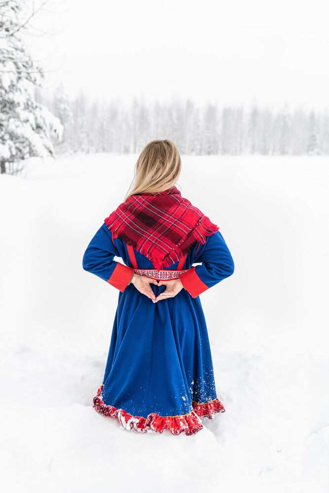 A girl wearing a plaid shawl stands in a snowy field.