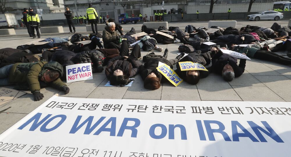 South Korean protesters lie on the ground during a rally to denounce a recent U.S. attack on Iran near the U.S. embassy in Seoul, South Korea, Friday, Jan. 10, 2020