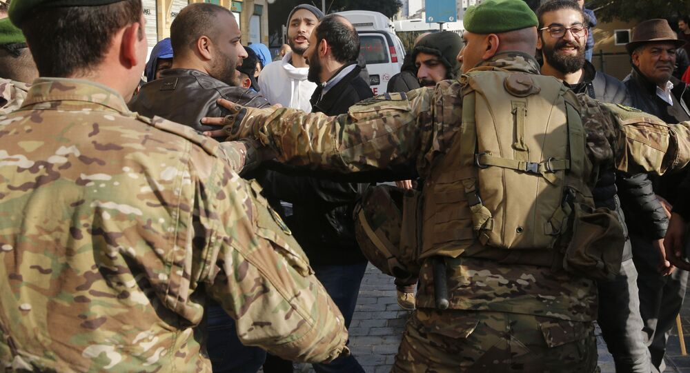 Lebanese army soldier push back the supporters of outgoing Prime Minister Saad Hariri, during an anti-government protest outside of the Beirut municipality in Lebanon, Friday, Jan. 10, 2010. Scuffles broke out between anti—government protesters calling for the ouster of the city's mayor and the governor of the province, and supporters of outgoing Prime Minister Saad Hariri, who handpicked them.