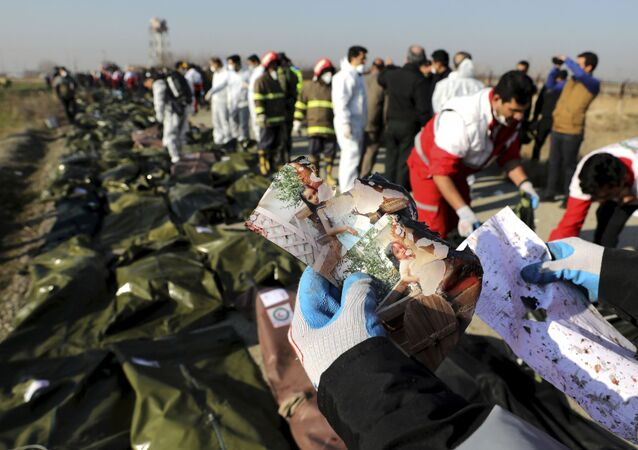 A rescue worker shows pictures of a girl recovered from a Ukrainian plane crash site in Shahedshahr, southwest of the capital Tehran, Iran