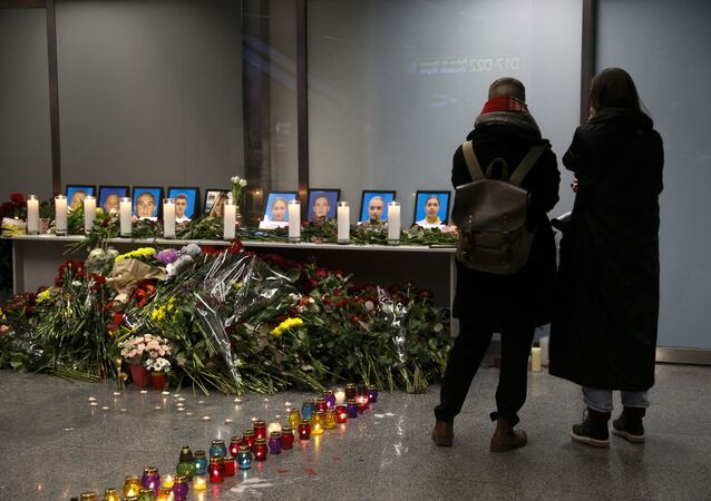 Two women mourn standing in front of a memorial for the flight crew of the Ukrainian 737-800 plane that crashed on the outskirts of Tehran, inside Borispil international airport outside Kyiv, Ukraine, late Wednesday, Jan. 8, 2020