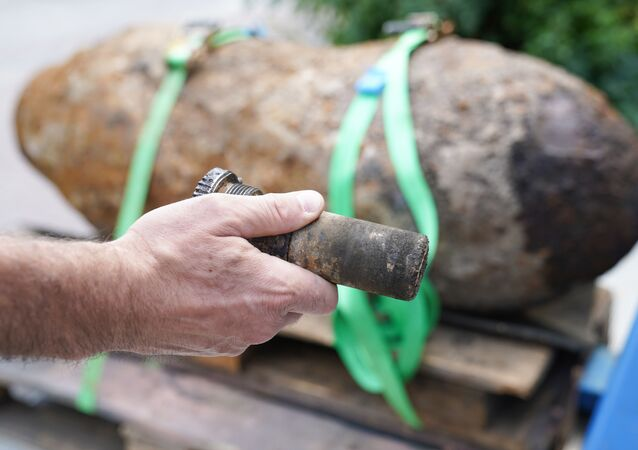 Marco Ofenstein from Rhineland-Palatinate's bomb disposal team presents the fuze of a World War II aerial bomb after the bomb's disposal in Ludwigshafen, western Germany, on 26 August 2018.