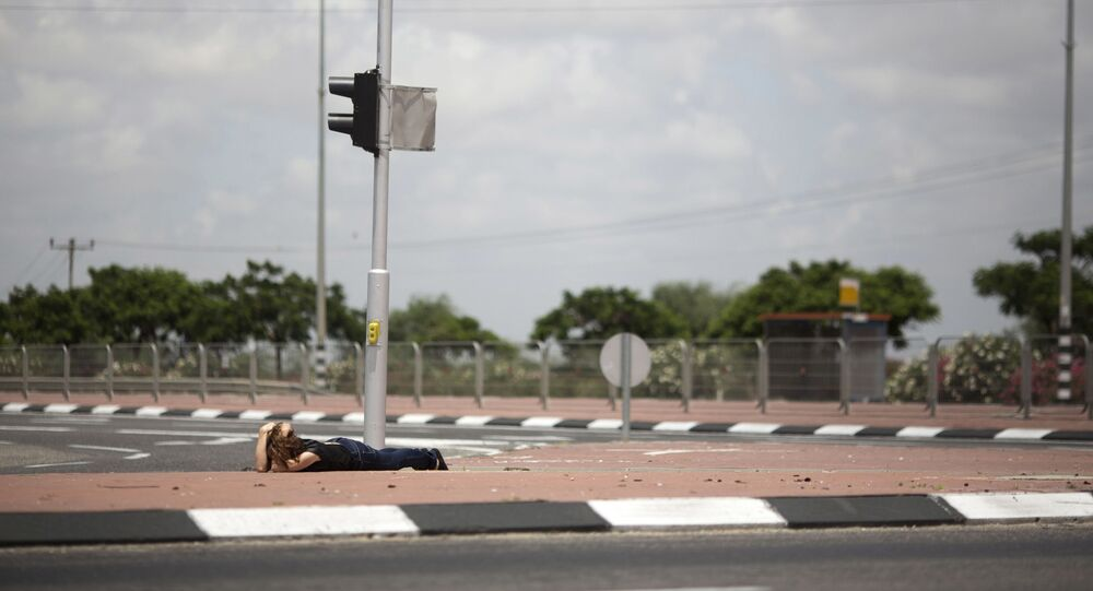 An Israeli woman takes cover as siren alarming sounds warning of rocket attacks by Palestinians militants from Gaza Strip in Ashkelon, southern Israel, Monday, July 14, 2014.