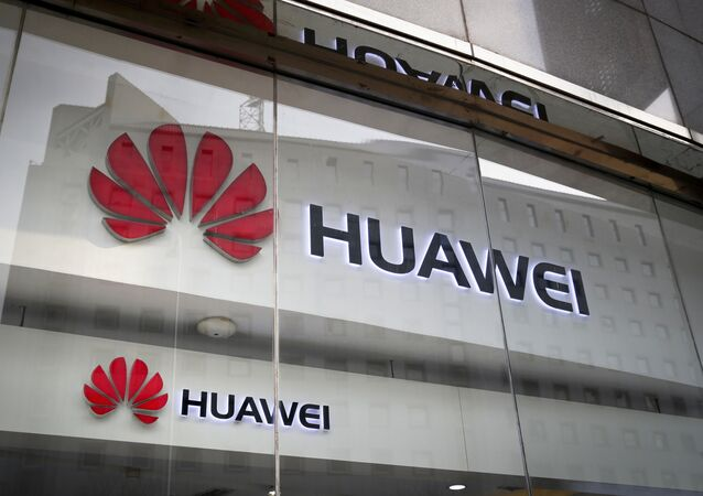 In this Jan. 29, 2019, file photo, the logos of Huawei are displayed at its retail shop window reflecting the Ministry of Foreign Affairs office in Beijing.