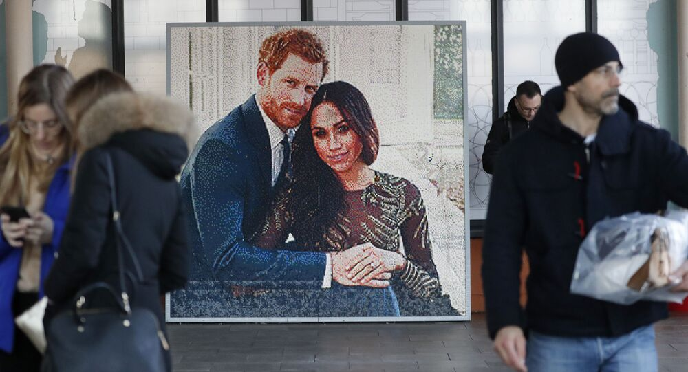 People walk past a picture of Britain's Prince Harry and Meghan Duchess of Sussex, in Windsor, Friday, Jan. 10, 2020. Britain's Prince Harry and his wife, Meghan, said they are planning to step back as senior members of the royal family and work to become financially independent.