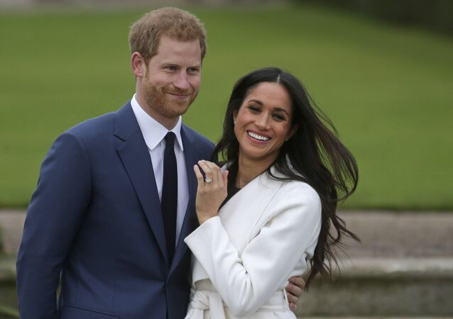 In this file photo Britain's Prince Harry stands with his fiance US actress Meghan Markle as she shows off her engagement ring whilst they pose for a photograph in the Sunken Garden at Kensington Palace in west London on November 27, 2017, following the announcement of their engagement