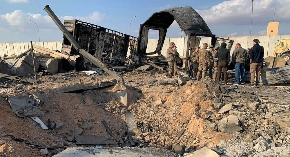 U.S. Soldiers and journalists stand near a crater caused by Iranian bombing at Ain al-Asad air base, in Anbar, Iraq, Monday, Jan. 13, 2020