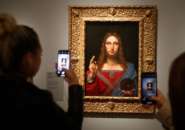 People take pictures with mobile phone at an oil painting by Atelier Leonardo da Vinci's   Salvator Mundi (Version Ganay), during the opening of the exhibition  Leonardo da Vinci , on October 22, 2019 at the Louvre museum in Paris
