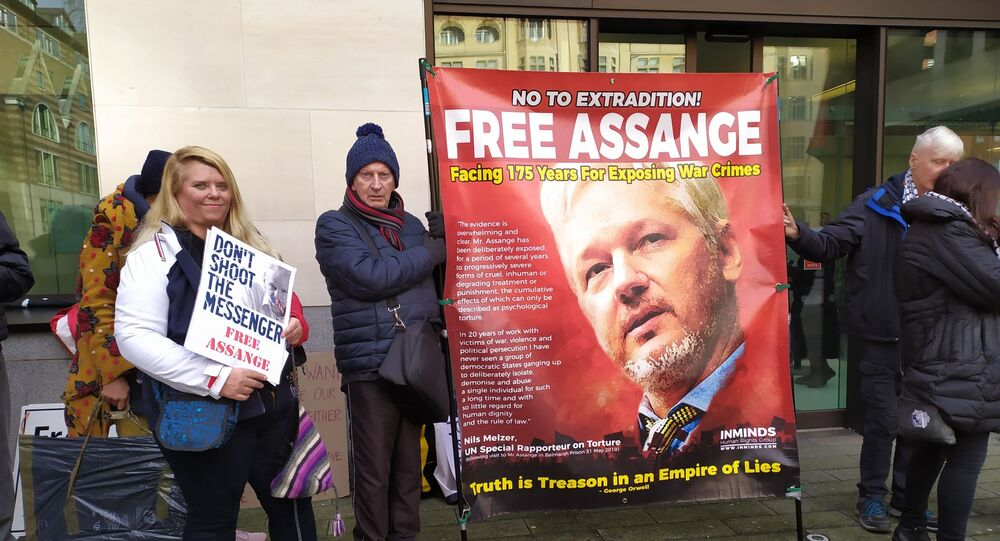 Demonstrators stand outside Westminster Magistrates Court with banners displaying their support for Assange