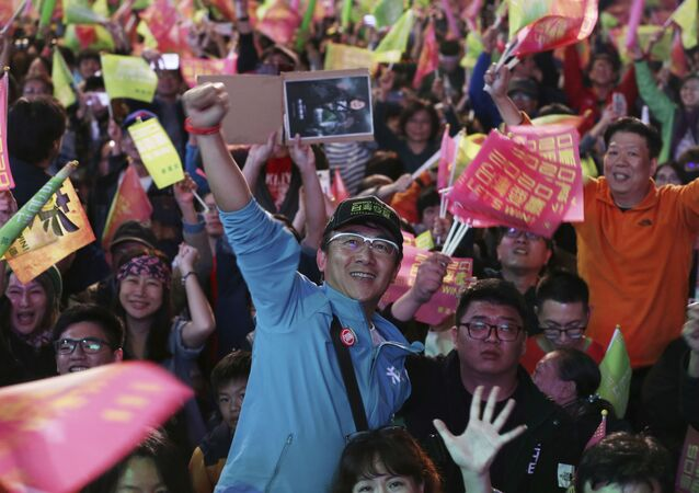 Supporters of Taiwan's 2020 presidential election candidate, Taiwan president Tsai Ing-wen cheer for Tsai's victory in Taipei, Taiwan, Saturday, Jan. 11, 2020. (AP Photo/Chiang Ying-ying)