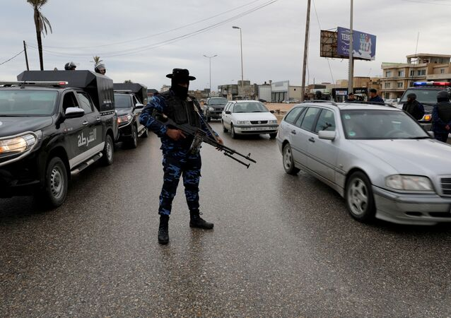 A member of the central security support force holds a weapon during a security deployment in the Tajura neighborhood