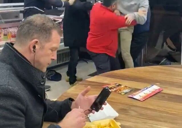 A man sits calmly during a fight at a kebab shop, England