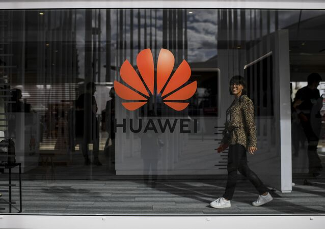 A woman walks past the logo of Chinese telecom giant Huawei during the Web Summit in Lisbon on November 6, 2019