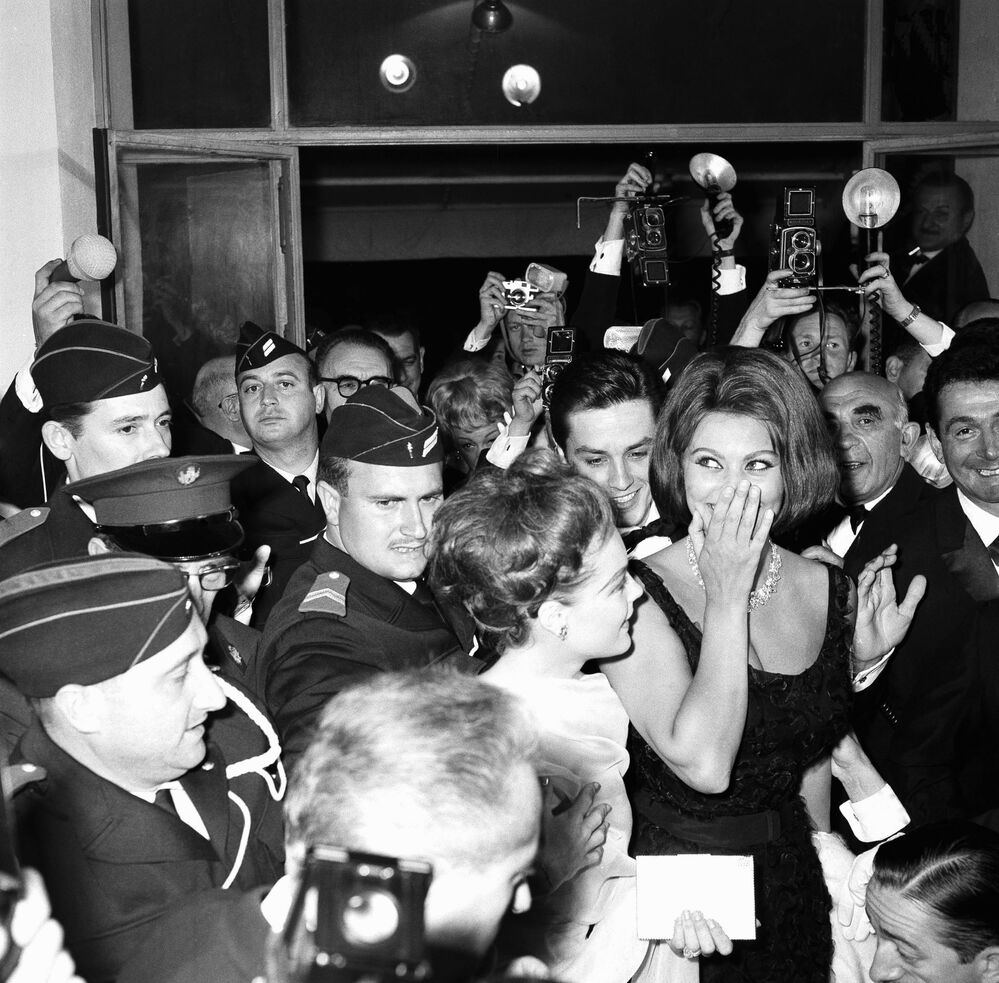 Italian Oscar-winning actress Sophia Loren, extreme right, and her company are protected by police from crushing crowds as they arrive at Festival Palace for the opening of the Cannes film festival, May 7, 1962. Next to Miss Loren is actress Romy Schneider and behind them is actor Alain Delon.