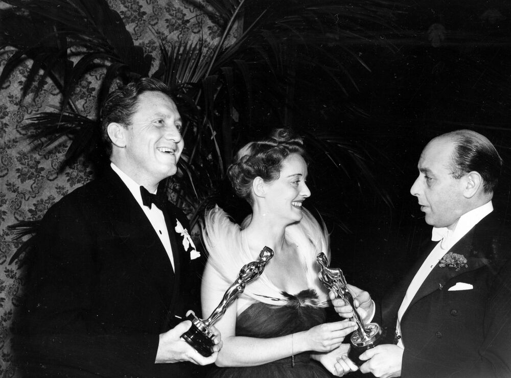 British actor Sir Cedric Hardwicke, right, presents the Oscar to Bette Davis and Spencer Tracy, left, at the 1938 Annual Academy Awards at the Biltmore Bowl, Biltmore Hotel in Los Angeles, Ca., Feb. 23, 1939. Davis, named best actress for her role in Jezebel, and Tracy, named best actor for his role in Boys Town, win an Oscar for their second consecutive year.