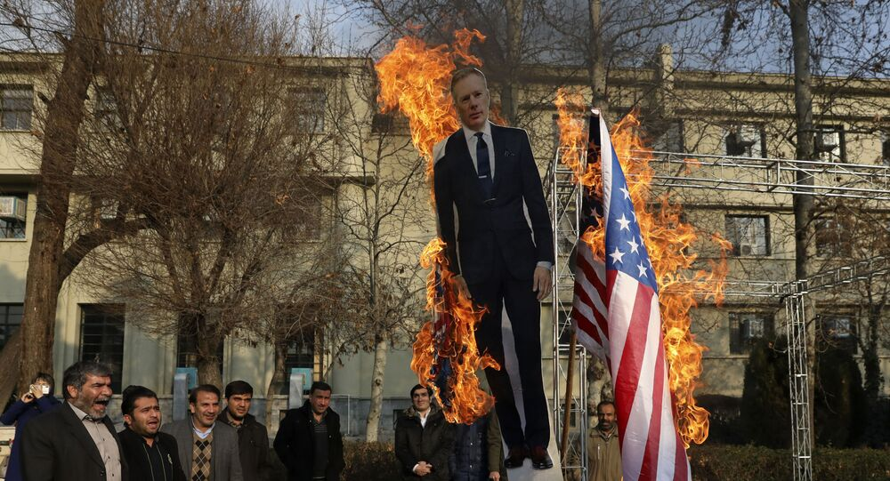 Pro-government protesters set fire to U.S. and British flags with a life size cut-out of Britain's ambassador to Tehran Rob Macaire, in a gathering to commemorate the late Iranian Gen. Qassem Soleimani, who was killed in Iraq in a U.S. drone attack on Jan. 3, and victims of last week's Ukrainian plane crash outside Tehran, at the Tehran University campus in Tehran, Iran, Tuesday, Jan. 14, 2020