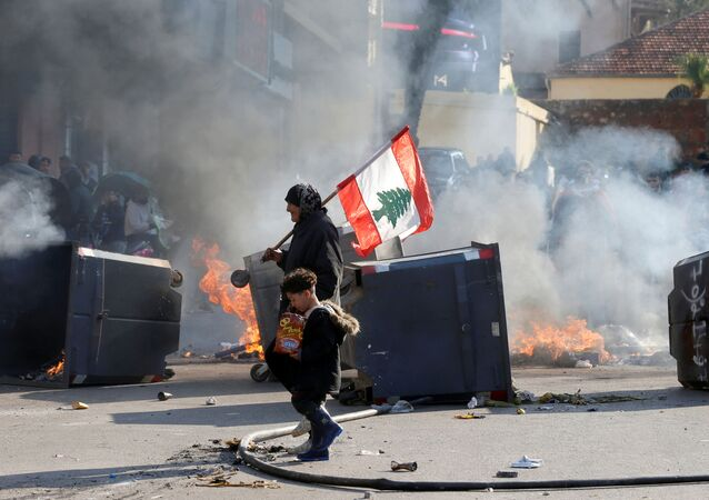 A protestor holding the Lebanese flag walks near burning barricades during a protest over economic hardship and lack of a new government in Beirut, Lebanon January 14, 2020.