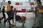 Passengers walk past the sales centre of AirAsia at Kempegowda International Airport in Bangalore, India, Wednesday, May 30, 2018