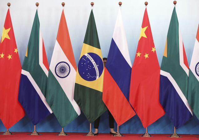 Staff worker stands behinds national flags of Brazil, Russia, China, South Africa and India to tidy the flags ahead of a group photo during the BRICS Summit at the Xiamen International Conference and Exhibition Center in Xiamen, southeastern China's Fujian Province, Monday, Sept. 4, 2017.
