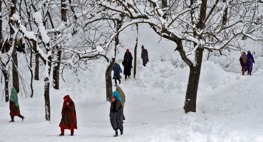 People walk through a snow-covered orchard to attend the funeral of Adil Ahmad, a suspected militant, who according to local media was killed in a gun battle with Indian soldiers, in Dalwan village in central Kashmir's Budgam district January 14, 2020