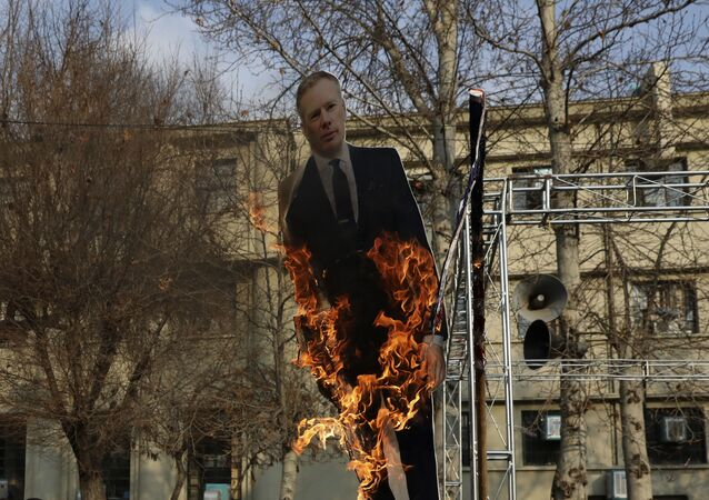 Pro-government protesters set fire to a life size cut out of Britain's ambassador to Tehran Rob Macaire at a gathering to commemorate the late Iranian Gen. Qassem Soleimani, who was killed in Iraq in a U.S. drone attack on Jan. 3, and victims of the Ukrainian plane that was mistakenly downed by the Revolutionary Guard last Wednesday, at the Tehran University campus in Tehran, Iran, Tuesday, Jan. 14, 2020