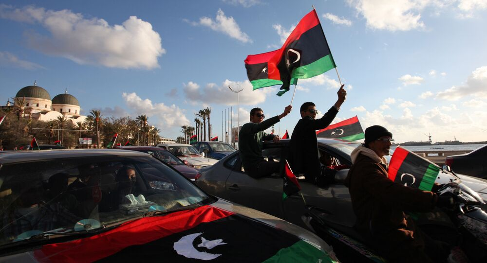 Libyans wave the national flag during commemorations to mark the second anniversary of the revolution that ousted Moammar Gadhafi in Benghazi, Libya, Friday, Feb, 15, 2013