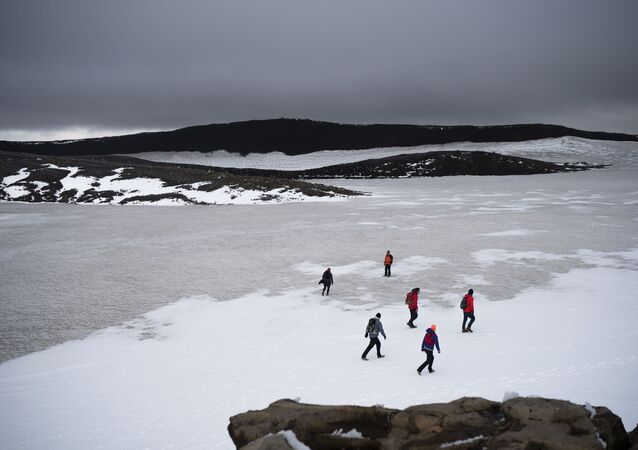 People walk on snow atop the Ok volcano crater on their way to a ceremony  by the area which once was the Okjokull glacier, in Iceland