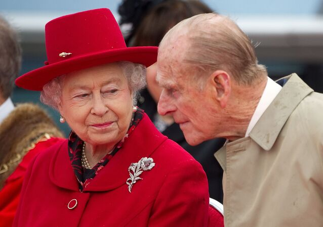 Britain's Queen Elizabeth speaks to her husband Prince Philip as they attend the official re-opening of the Cutty Sark in Greenwich, London  April 25, 2012.
