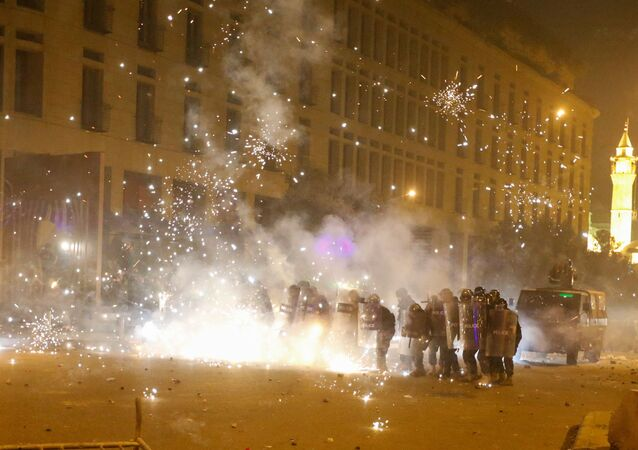 Fireworks are set off in front of police officers standing in postion behind riot shields during a protest against a ruling elite accused of steering Lebanon towards economic crisis in Beirut, Lebanon January 18, 2020.