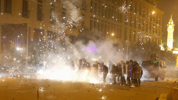 Fireworks are set off in front of police officers standing in postion behind riot shields during a protest against a ruling elite accused of steering Lebanon towards economic crisis in Beirut, Lebanon January 18, 2020.  - Sputnik International