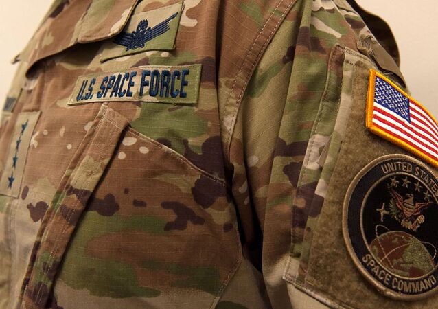 A military camouflage uniform bearing a U.S. Space Force nametape and U.S. Space Command shoulder patch