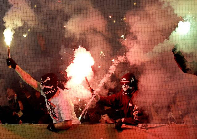 Supporters of St. Pauli light fireworks during the German soccer cup second round match between FC St. Pauli and Borussia Dortmund