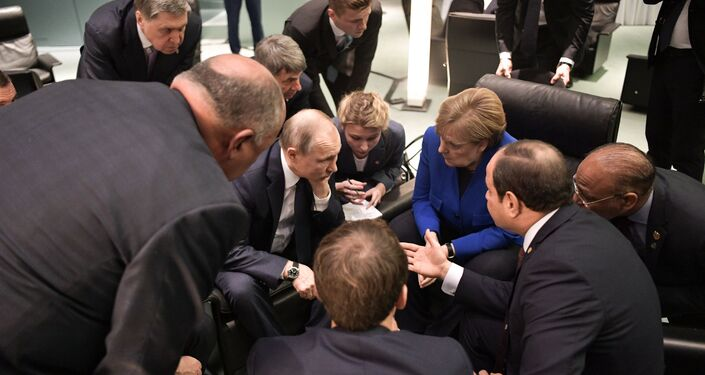 Russian President Vladimir Putin and German Chancellor Angela Merkel speak during a meeting on the sidelines of an international peace conference on Libya in Berlin, Germany.