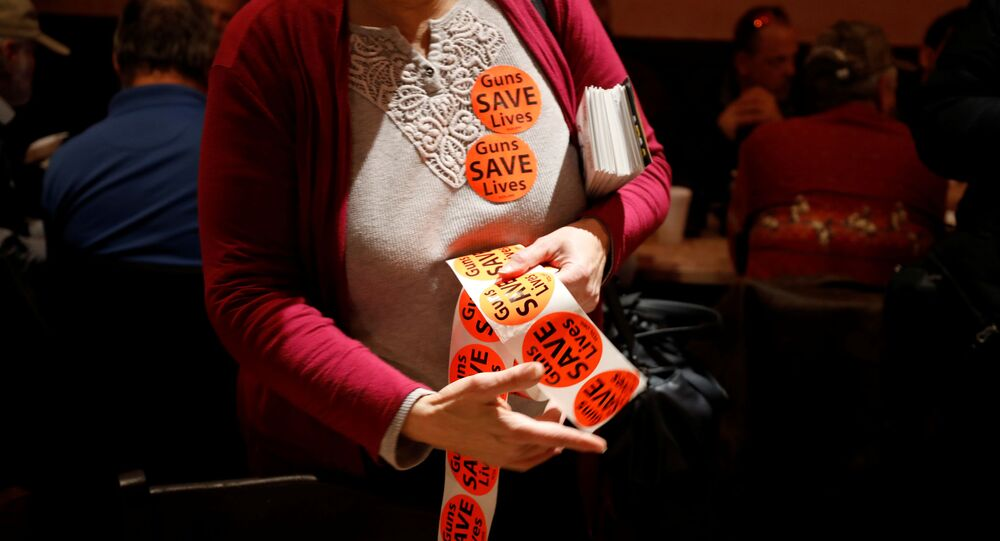 A member of the Virginia Citizens Defense League distributes Guns Save Lives stickers during the organization's Sunday dinner before their Monday rally at Virginia's Capitol, in Henrico, Virginia, U.S. January 19, 2020