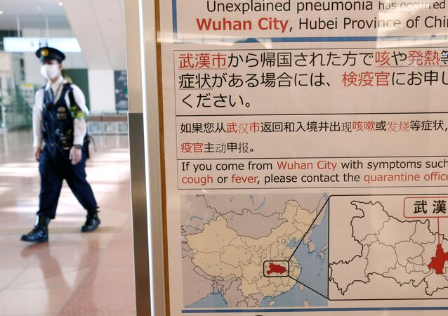 A policeman wearing a mask walks past a quarantine notice about the outbreak of coronavirus in Wuhan, China at an arrival hall of Haneda airport in Tokyo, Japan, January 20, 2020.