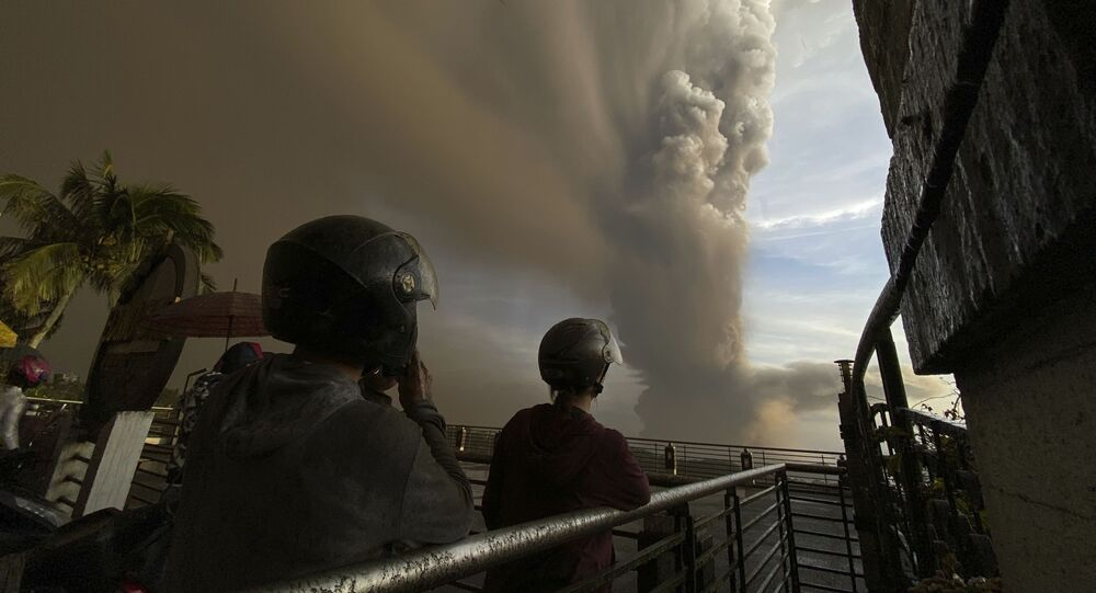 In this Jan. 12, 2020, photo, people watch plumes of smoke and ash rise from as Taal volcano erupts in Tagaytay, Cavite province, outside Manila, Philippines