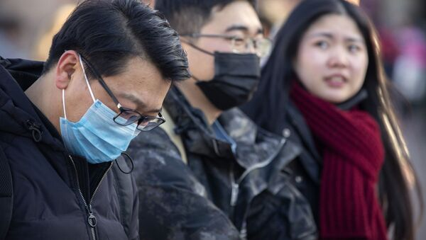 Travelers wear face masks as they walk outside of the Beijing Railway Station in Beijing, Monday, Jan. 20, 2020. China reported Monday a sharp rise in the number of people infected with a new coronavirus, including the first cases in the capital. The outbreak coincides with the country's busiest travel period, as millions board trains and planes for the Lunar New Year holidays. - Sputnik International