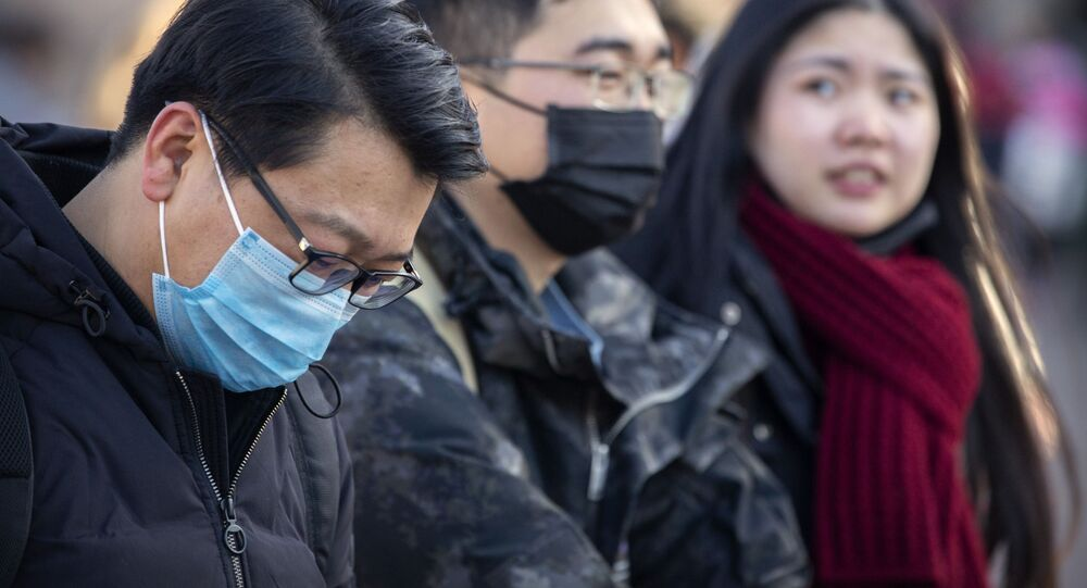 Travelers wear face masks as they walk outside of the Beijing Railway Station in Beijing, Monday, Jan. 20, 2020. China reported Monday a sharp rise in the number of people infected with a new coronavirus, including the first cases in the capital. The outbreak coincides with the country's busiest travel period, as millions board trains and planes for the Lunar New Year holidays.