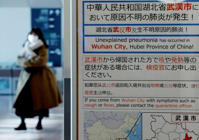 A woman wearing a mask walks past a quarantine notice about the outbreak of coronavirus in Wuhan, China at an arrival hall of Haneda airport in Tokyo, Japan, January 20, 2020