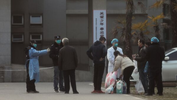 Medical staff and security personnel stop patients' family members from being too close to the Jinyintan hospital, where the patients with pneumonia caused by the new strain of coronavirus are being treated, in Wuhan, Hubei province, China January 20, 2020 - Sputnik International