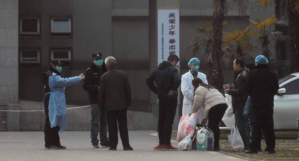 Medical staff and security personnel stop patients' family members from getting too close to the Jinyintan hospital, where patients with pneumonia caused by the new strain of coronavirus are being treated, in Wuhan, Hubei province, China, 20 January 2020