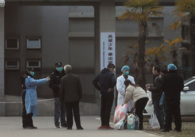 Medical staff and security personnel stop patients' family members from being too close to the Jinyintan hospital, where the patients with pneumonia caused by the new strain of coronavirus are being treated, in Wuhan, Hubei province, China January 20, 2020