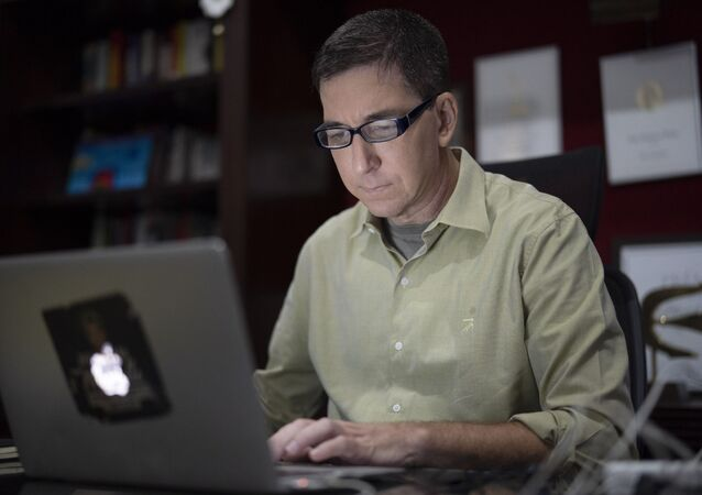 In this 10 July 2019 file photo, U.S. journalist Glenn Greenwald checks his news website at his home in Rio de Janeiro, Brazil.