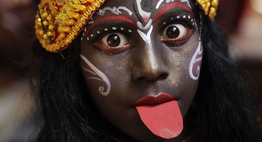 In this Friday, April 13, 2018, file photo, a girl dressed as Hindu goddess Kali waits to join a religious procession during a ritual of Shiva Gajan Hindu festival in Kolkata, India
